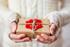 Woman in sweater and mitts holds a present with crocheted snowflake. Royalty Free Stock Photography