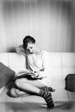 Woman in sweater reading a book on sofa Royalty Free Stock Image