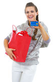Woman in sweater with shopping bag showing credit card Stock Photography