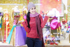 Woman with sweater and shopping bags at mall Stock Images