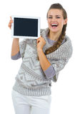 Woman in sweater showing tablet PC blank screen Stock Images