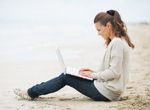 Woman in sweater sitting on beach and using laptop Stock Image