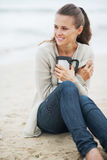 Woman in sweater sitting on lonely beach with cup of beverage Stock Images