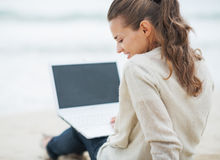 Woman in sweater sitting on lonely beach and using laptop Stock Photo