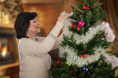 Woman in sweater tinsels Christmas tree Royalty Free Stock Images