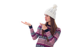 Woman in sweater and white hat holding something. Young attractive woman in purple sweater and white hat holding something on her hand on white background in Royalty Free Stock Photo
