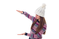 Woman in sweater and white hat holding something. Young beautiful woman in purple sweater and white hat holding something on white background in studio Royalty Free Stock Photo