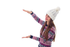 Woman in sweater and white hat holding something Royalty Free Stock Images