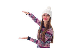 Woman in sweater and white hat holding something. Young nice woman in purple sweater and white hat holding something on white background in studio Stock Images