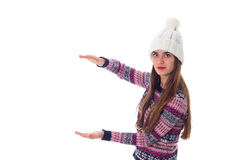 Woman in sweater and white hat holding something. Young nice woman in purple sweater and white hat holding something on white background in studio Stock Image