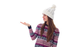 Woman in sweater and white hat holding something. Young nice woman in purple sweater and white hat holding something on her hand on white background in studio Stock Images