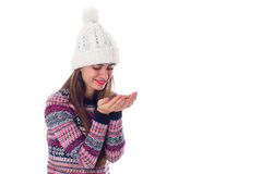 Woman in sweater and white hat holding something. Young nice woman in purple sweater and white hat holding something in her hands on white background in studio Royalty Free Stock Photo