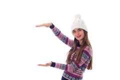 Woman in sweater and white hat holding something. Young positive woman in purple sweater and white hat holding something on white background in studio Royalty Free Stock Images