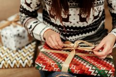 Woman in sweaters with deers openning christmas presents under t Royalty Free Stock Images