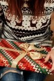 Woman in sweaters with deers openning christmas presents under t Stock Photo