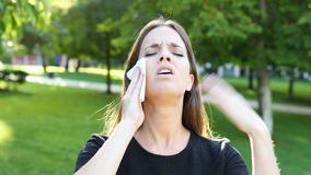 Woman sweating and suffering heat stroke. Overwhelmed woman sweating and suffering heat stroke walking in a park a warm summer day stock footage