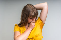 Woman with sweating under armpit in yellow dress. Young woman with sweating under armpit in yellow dress isolated on gray Stock Image