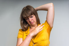 Woman with sweating under armpit in yellow dress. Young woman with sweating under armpit in yellow dress isolated on gray Stock Photos