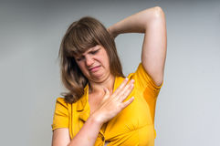 Woman with sweating under armpit in yellow dress. Young woman with sweating under armpit in yellow dress isolated on gray Stock Images