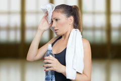 Woman sweating. After workout holding a glass of water Royalty Free Stock Photo