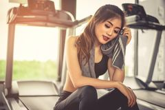 Woman sweats by towel during rest in fitness gym with fitness ru royalty free stock photos