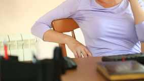 Woman with sweaty armpits. Girl sitting at the working place in office and sweating stock footage