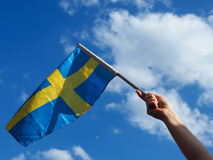 Woman with the Swedish flag. Female hand waving with the Swedish flag on a blue summer sky Royalty Free Stock Image