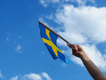 Woman with the Swedish flag. Female hand waving with the Swedish flag on a blue summer sky Royalty Free Stock Photos