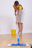Woman sweeping. The floor with a domestic broom Royalty Free Stock Image