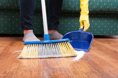 Woman sweeping floor with broom and dustpan Stock Photo