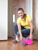 Woman sweeping the floor Stock Images
