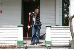 Woman sweeping front porch. Young woman sweeps front porch of balcony with broom Stock Images
