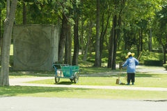 Woman sweeping leave on lawn. In the garden Royalty Free Stock Photo