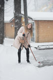 Woman sweeping the snowy street Royalty Free Stock Photography