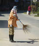 Woman sweeping the street Royalty Free Stock Images