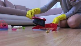Woman sweeps the dirty floor. In room stock video footage