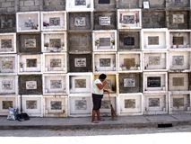 A woman sweeps in front of columns of graves in a cemetery in Antipolo City, Philippines. ANTIPOLO CITY, PHILIPPINES - MARCH 18, 2016: A woman sweeps in front of royalty free stock images