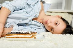 Woman with sweet cake. Sad overeat young woman with sweet cake lying on bed Royalty Free Stock Photo
