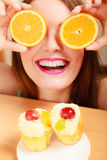 Woman with sweet cakes and orange covering eyes. Stock Images