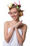 Woman with a sweet face and curlers on hair. Royalty Free Stock Photos