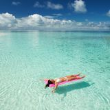Woman swim and relax in the sea. Happy island lifestyle. White sand, crystal-blue sea of tropical beach. Vacation at Paradise. stock photos