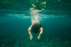 Woman swim underwater. Free diving into the water stock image