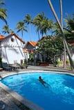 Woman  swiming in pool at tropical resort. Young woman  swiming in pool at tropical resort Stock Images