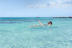 Woman swiming in the sea at Elafonisi beach, in the island of Cr. Ete, in summer stock photography