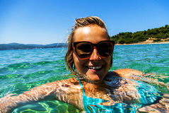 Woman swiming in the sea on tropical island, smiling at camera w Stock Photo
