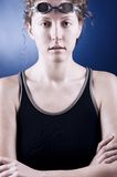 Woman swimmer. Portrait of a looking at camera woman swimmer with folded hands, blue toned on blue background Royalty Free Stock Photography