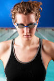 Woman swimmer. Portrait of a woman swimmer looking at camera with blurred swimming pool behind her Stock Image