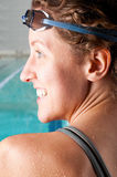 Woman swimmer. Portrait of a woman swimmer looking at camera with blurred swimming pool behind her Royalty Free Stock Photography