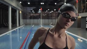 Woman swimmer dive in water pool at start. Swimmer jump at deep water pool. Woman swimmer dive in water pool at start slow motion. Close up female swimmer stock video