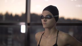 Woman swimmer putting goggles on face for underwater swimming in pool. Close up woman swimmer putting on head glasses for floating pool 60 fps stock footage